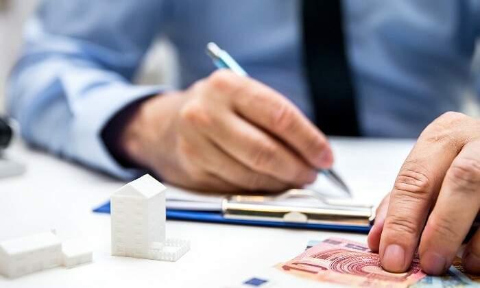 700x420 hombre firma dinero casitas istock